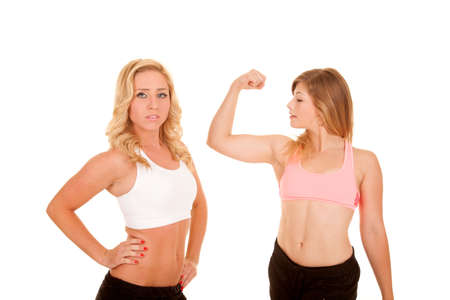bod: two women posing in their fitness clothing, one is flexing her muscles.