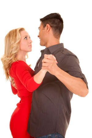 A woman and man looking into each others eyes dancing.