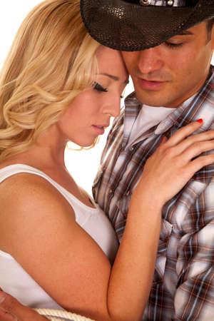 coppia romantica: un cowboy aggrappato alla sua ragazza vicino guardando in basso. Archivio Fotografico