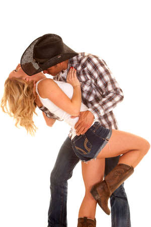 a cowboy leaning his woman back getting ready to kiss her neck.