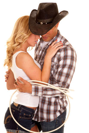 a cowboy and his girl tied up together, being close together.