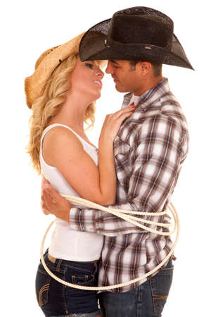 A cowboy getting ready to lean in for a kiss on his cowgirl.  They are tied up by a rope.