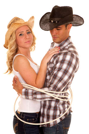 A cowboy and cowgirl tired up with a rope, getting\ close.