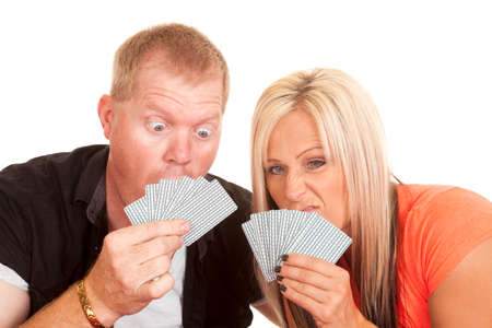 a man and woman with funny expressions looking at their playing cards. photo