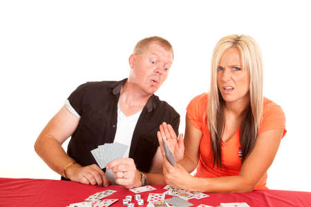 A man and woman playing cards, the man is trying to peek at the woman's cards.