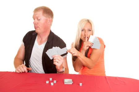 A woman is trying to sneak a card from the mans hands. photo