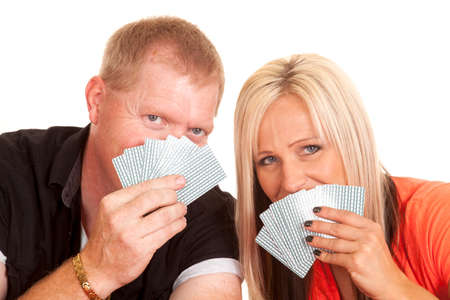 A man and woman leaning heads close, while their mouths are covered by playing cards. photo