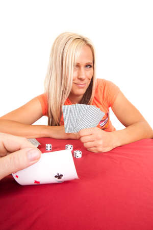 A person is looking at his cards with a woman in the background. photo