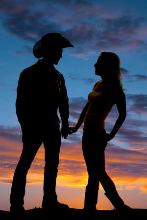 A silhouette of a cowboy and his woman holding hands in the outdoors.