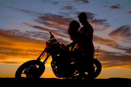 A man looking down at his woman, as she sits on a motorbike, looking into her eyes. photo