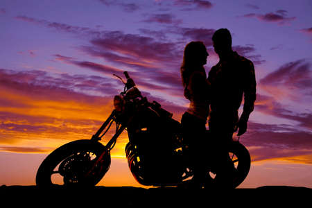 motorcycle: A silhouette of a man and woman next to a motorcycle in the outdoors.