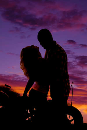 a silhouette of a man and woman getting close on the back of a motorcycle. photo