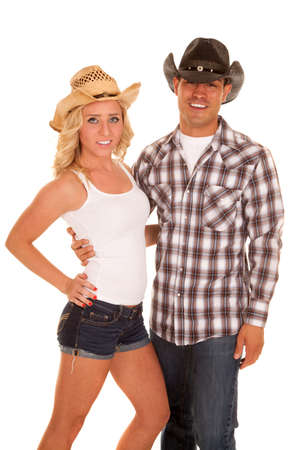 a cowgirl and cowboy with smiles they are holding on to each other.