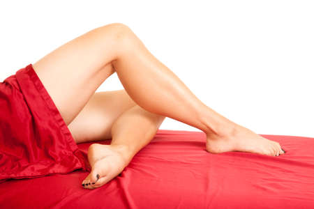 white sheet: A womans legs curled under each other on a red sheet