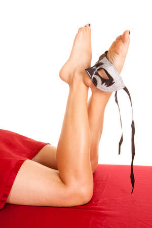 A womans legs and feet on a red sheet holding a mask. photo