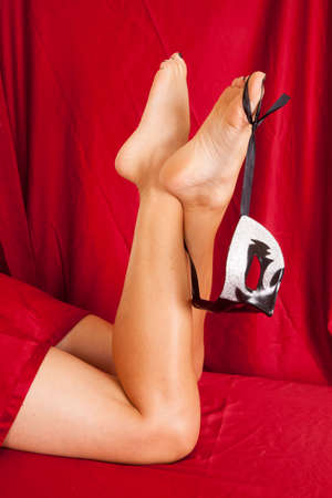 A womans legs under a red sheet holding on to a mask. photo