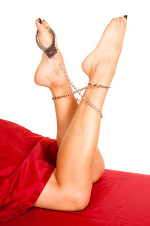 cuffs: A woman in her bed with hand cuffs on her ankles and toe. Stock Photo