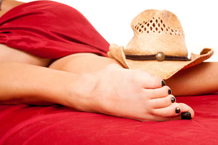 long toes: a woman under a red sheet, with a straw hat on her legs. Stock Photo