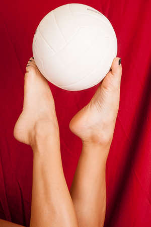 A woman with her legs up with a red sheet holding on to a volleyball. Imagens