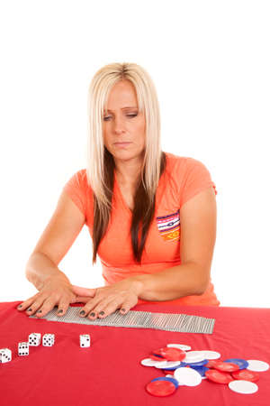 A woman laying out cards on a table with dice and chips, getting ready for a game. photo