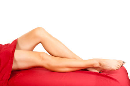 long toes: A woman showing her legs out from under a red sheet.