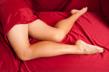 white sheet: A woman laying on a red sheet showing off her legs. Stock Photo