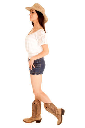 A cowgirl standing with her eyes closed in her short denim shorts and boots.