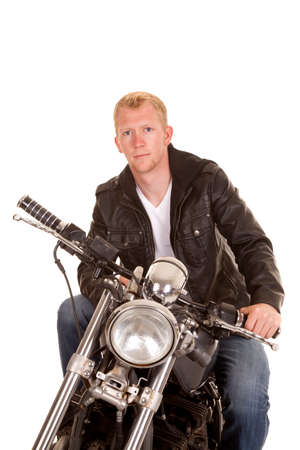 A man sitting on his motorcycle with a serious expression on his face. Stock Photo