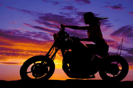 A silhouette of a woman on a motorcycle sitting with the wind blowing through her hair.