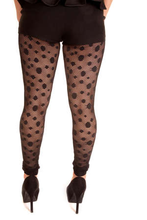 A back view of a woman in her sheer see through polka dot leggings.