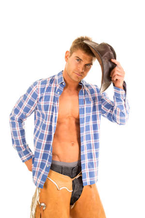 shirt unbuttoned: A cowboy with a serious expression, holding on to his hat with his shirt unbuttoned.