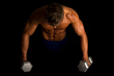 A man doing  a push up on weights, showing his muscles.