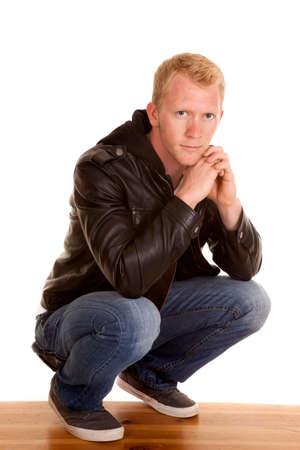 A man kneeling down low in his leather jacket.