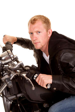 leaning forward: a man sitting on his motorcycle leaning forward on his bike.