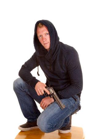 man kneeling: A man kneeling with a pistol across his leg.