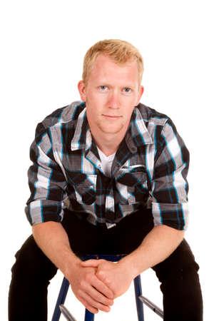 leaning forward: A man in his plaid shirt leaning forward, sitting on a blue chair.