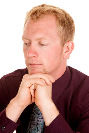 deep thought: A man in his business clothing with his hands up by his chin in deep thought.