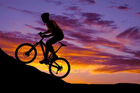 a silhouette of a man riding a mountain bike up a hill. Archivio Fotografico