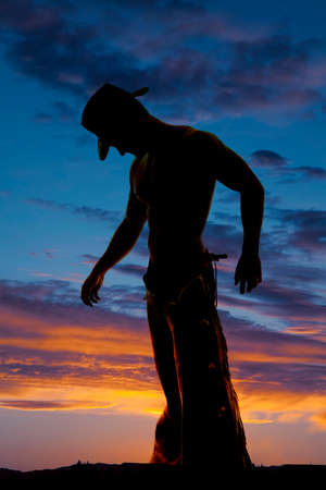A silhouette of a cowboy with his head down in the outdoors. Stock Photo