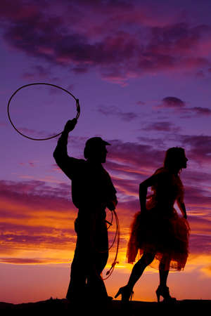 A silhouette of a cowboy getting ready to rope his lady.
