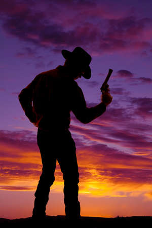 A silhouette of a man holding on to his pistol in the outdoors. photo
