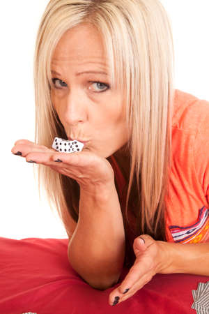 a woman kissing her dice in her hand for good luck. Stock Photo