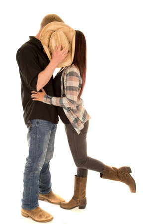 gal: A cowboy blocking the view of the camera, while he kisses his gal. Stock Photo