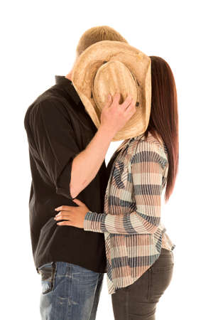 A couple hiding behind a cowboy hat, getting a kiss.