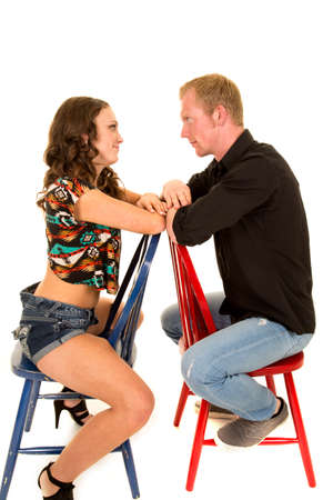 facing each other: a couple sitting on chars facing each other with their arms touching. Stock Photo