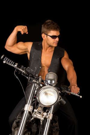 A man looking to the side flexing his muscles on his motorcycle.