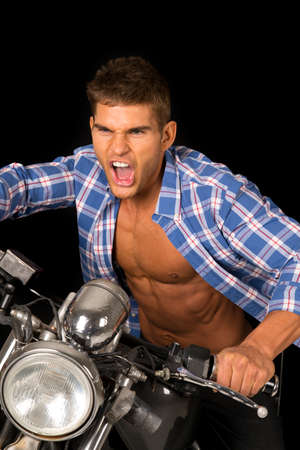 undone: A man on his motorcycle screaming with his shirt undone and the wind blowing his shirt.