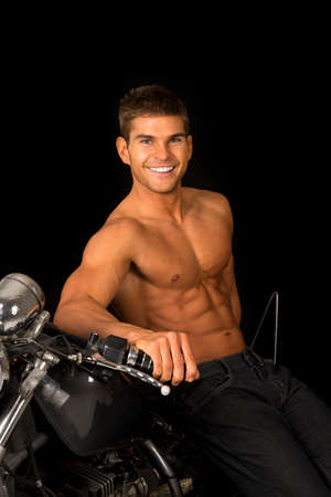 chrome man: a man leaning back on his motorcycle with out a shirt, smiling.