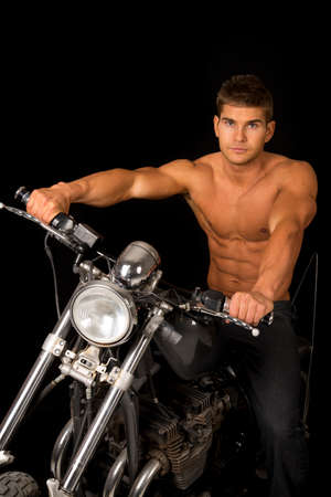 chrome man: A man sitting on his motorcycle with out a shirt on, with a serious expression.