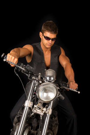 chrome man: A man sitting on his motorcycle wearing his black vest and sunglasses.